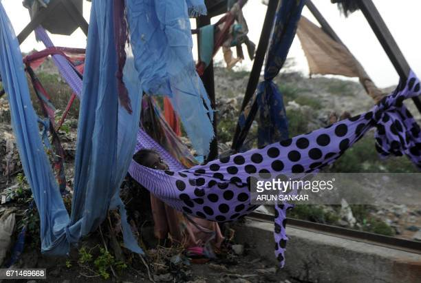 An Indian child lies in a hammock made from salvaged material at a garbage dump during Earth Day on the outskirts of Chennai on April 22 2017 Earth...