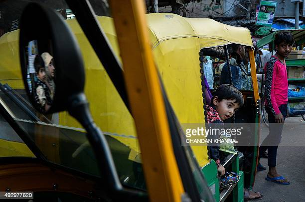 An Indian child looks at the street from a rickshaw in the old districts of New Delhi on October 16 2015 AFP PHOTO / Chandan KHANNA