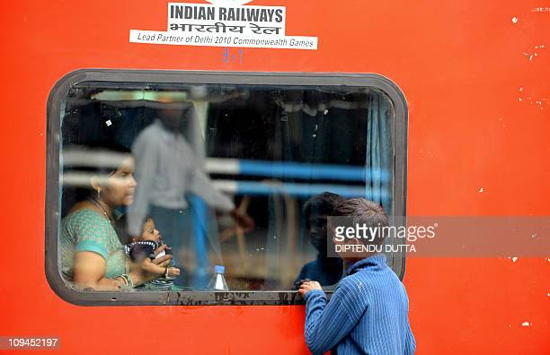 An Indian child looks on as a passenger sits inside The Rajdhani Express at New Jalpaiguri Railway Station in Siliguri on February 25 as Indian...