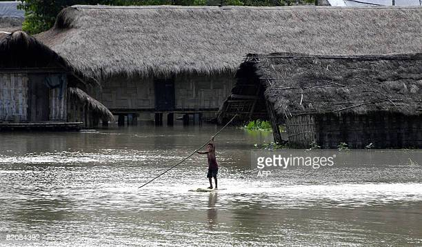 An Indian child paddles through floodwaters on a banana raft in the Matmara area of North Lakhimpur district some 470 kms east of Guwahati on July 26...