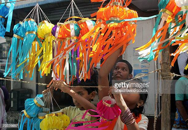 An Indian child Purva Hinglekar along with her brothers strings paper lanterns for sale on the eve of the Hindu festival of lights 'Diwali' in Mumbai...