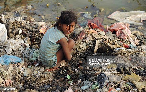 An Indian child searches for coins used in ritual offerings by Hindu devotees on the polluted banks of the river Yamuna in Allahabad on May 7 2010AFP...