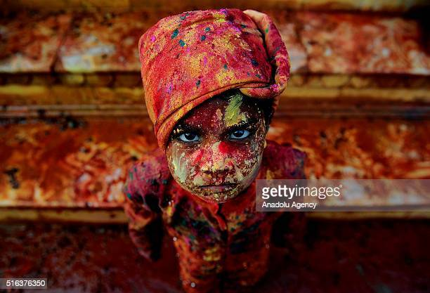 An Indian child smeared with coloured powder takes part in the Holi Festival celebrations in Mathura India on March 18 2016 Holi the festival of...