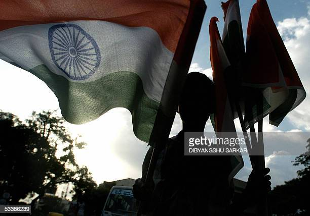 An Indian child street vendor is sillhouetted against the sky as he sells tricolour national flags at a traffic junction in Bangalore 14 August 2005...