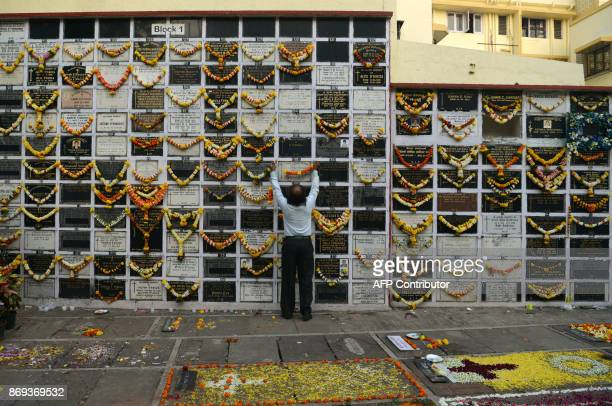 An Indian Christian devotee leaves a garland of flowers on a plaque commemorating relatives on All Souls Day at the cemetery of a church in Mumbai on...