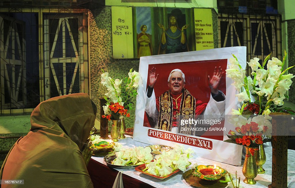 An Indian Christian devotee offers flowers to a picture of Pope Benedict XVI during a special prayer in a Church in Kolkata on February 26, 2013. The prayer was organised to wish the pope well after he steps down at the end of February 2013. AFP PHOTO/ Dibyangshu SARKAR