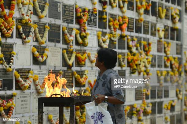 An Indian Christian devotee prays near a plaque commemorating relatives on All Souls Day at the cemetery of a church in Mumbai on November 2 2017 All...