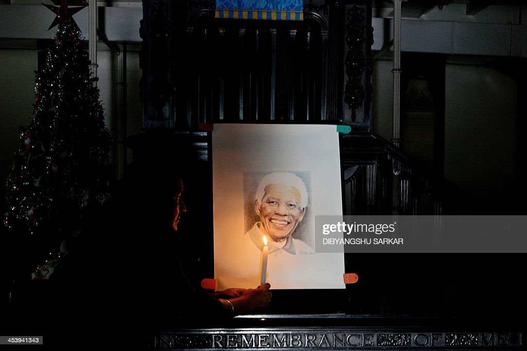 An Indian Christian holds a candle in front of a portrait of South African former president Nelson Mandela as a part of his homage inside a church in Kolkata on December 6, 2013. Mandela, the revered icon of the anti-apartheid struggle in South Africa and one of the towering political figures of the 20th century, has died aged 95. Mandela, who was elected South Africa's first black president after spending nearly three decades in prison, had been receiving treatment for a lung infection at his Johannesburg home since September, after three months in hospital in a critical state. AFP PHOTO/Dibyangshu SARKAR