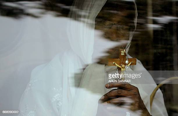 TOPSHOT An Indian Christian holds a cross as she takes part with others in a procession to reenact the crucifixion of Jesus Christ on the occasion of...