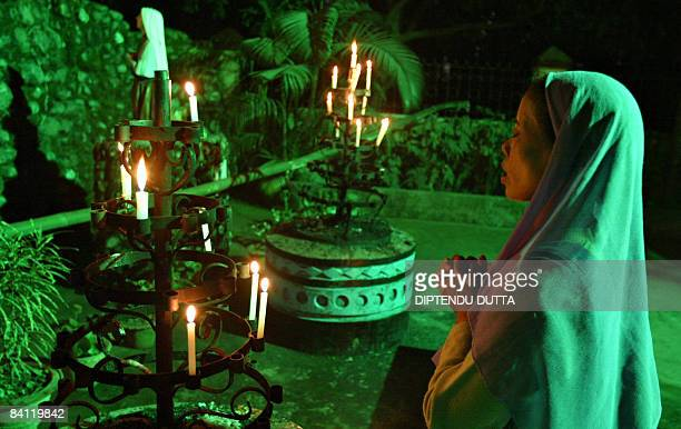 An Indian Christian woman prays after placing candles in front a statue of Jesus Christ at the St Mary's Church in Siliguri on Christmas eve December...