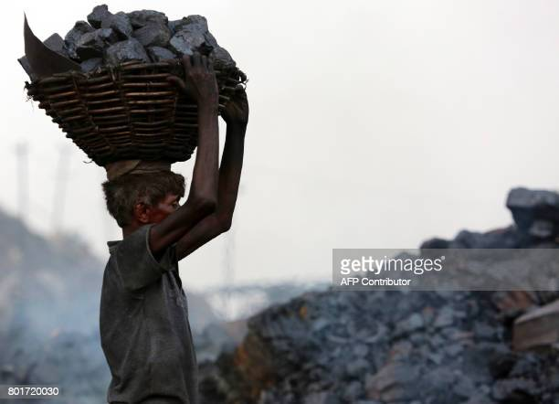 TOPSHOT An Indian coal scavenger carries a basket of coal collected at a mine in the district of Dhanbad in the state of Jharkhand on June 27 2017...