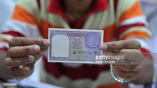An Indian collector displays an Indian one rupee note at a three day Coins Notes fair in Hyderabad on July 29 2011 More than 85 coin notes and stamp...