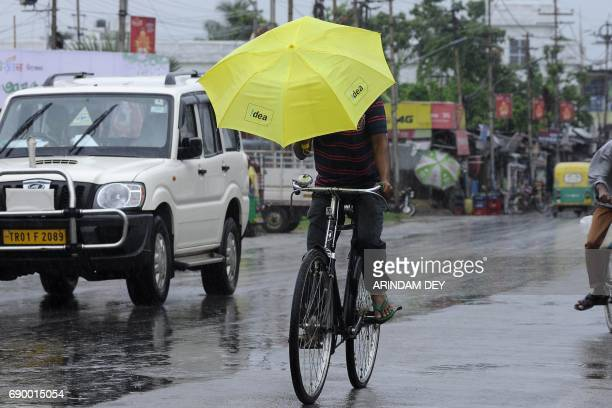 An Indian commuter holds an umbrella in front of his face as he rides a bicycle through heavy rain brought by Cyclone Mora in Agartala the capital of...