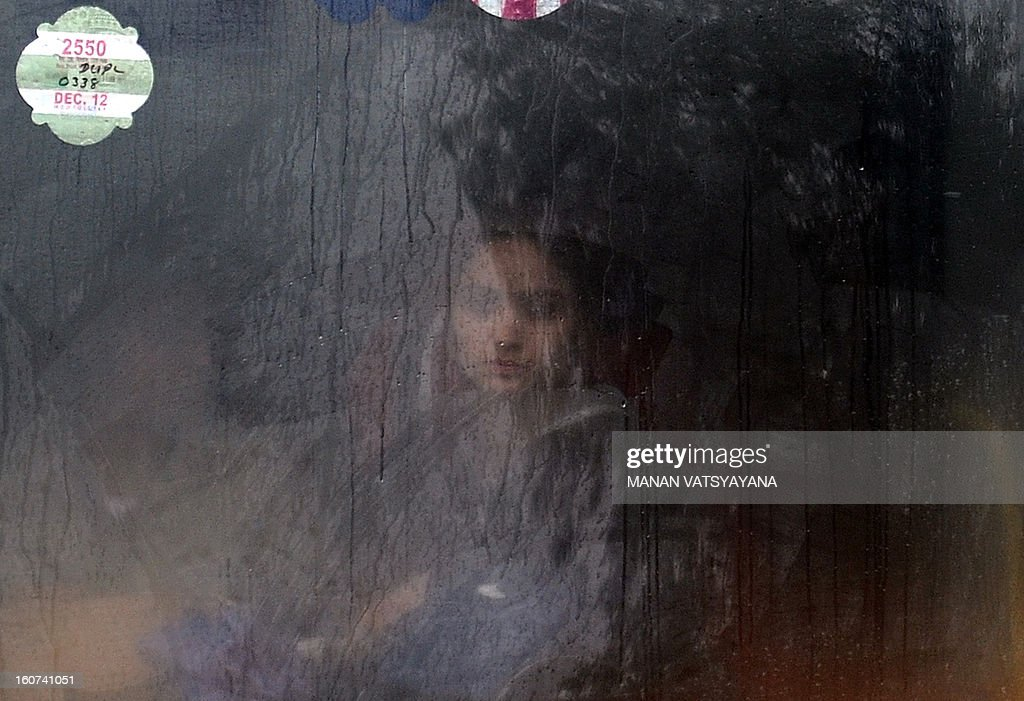An Indian commuter looks out from a bus window while travelling during a heavy downpour in New Delhi on February 5, 2013. Heavy rains lashed the Indian capital bringing down the mercury and throwing normal life out of gear. AFP PHOTO/ MANAN VATSYAYANA