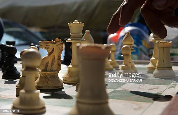 An Indian commuter plays a chess move during a game on the roadside in Kolkata on November 20 in an area popular with local chess enthusiasts who can...
