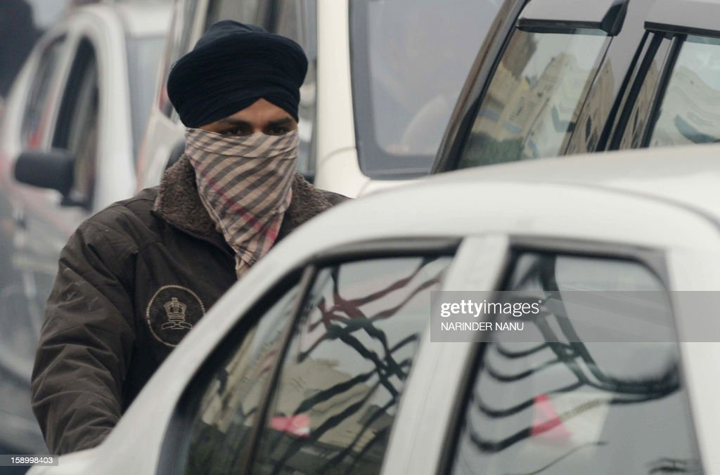 An Indian commuter protect his face from the cold weather, while driving on a motorbike in Amritsar on January 5, 2013. Winter fog and cold weather in parts of northern India have disrupted traffic, causing delays in flight and train schedules. AFP PHOTO/NARINDER NANU