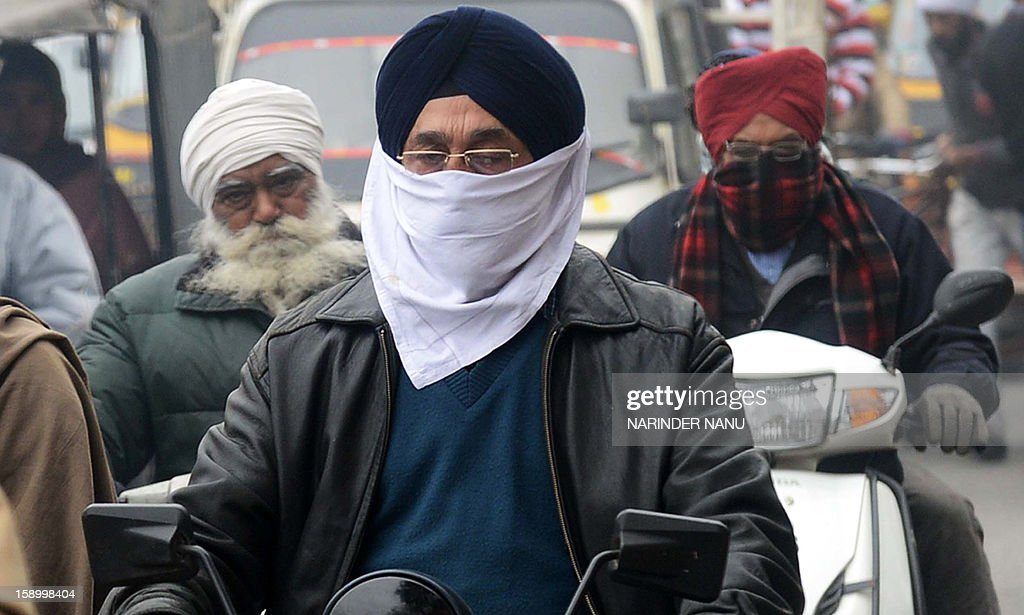 An Indian commuter protect his face from the cold weather, while driving on a motorbike in Amritsar on January 5, 2013. Winter fog and cold weather in parts of northern India have disrupted traffic, causing delays in flight and train schedules.