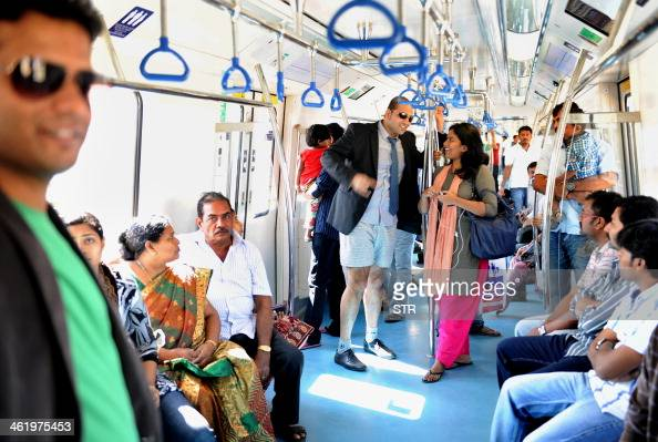 An Indian commuter stripped to his underpants chats to a fellow commuter as he takes part in a No Pants Subway Ride on the metro in Bangalore on...