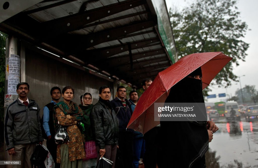 An Indian commuter (R) takes shelter under an umbrella as office-goers wait at a bus stop in New Delhi on February 5, 2013. Heavy rains lashed the Indian capital bringing down the mercury and throwing normal life out of gear.
