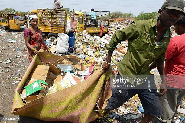 An Indian couple collect recyclable items at a garbage dump yard in Hyderabad on June 5 2014 on World Environment Day India's cities are becoming...
