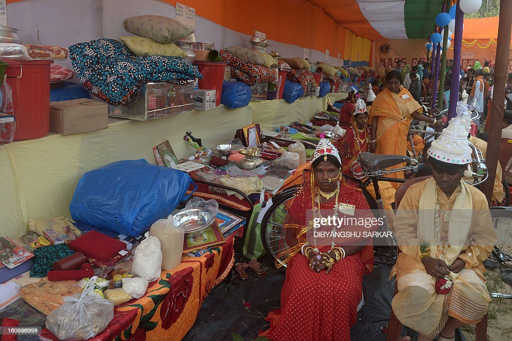 An Indian couple look on as they sit next to wedding gifts during a mass marriage ceremony in Haripal, some 70 kms north of Kolkata, on February 3, 2013. Some 108 couples from Hindu, Muslim, and tribal communities were married in the event organised by a charitable trust. AFP PHOTO/Dibyangshu Sarkar
