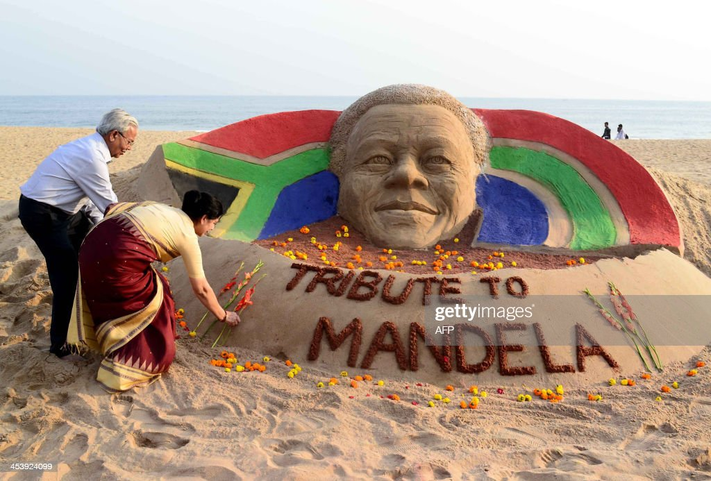 An Indian couple place flowers on a sand sculpture in tribute to former South African president Nelson Mandela, made by sand artist Sudarsan Pattnaik, at the Golden Sea Beach in Puri, some 65 kilometers away from Bhubaneswar, on December 6, 2013. Mandela, the revered icon of the anti-apartheid struggle in South Africa and one of the towering political figures of the 20th century, has died aged 95. Mandela, who was elected South Africa's first black president after spending nearly three decades in prison, had been receiving treatment for a lung infection at his Johannesburg home since September, after three months in hospital in a critical state.
