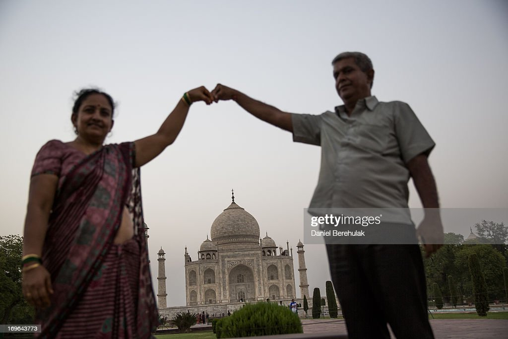 An Indian couple pose for a photograph as they visit the Taj Mahal on May 29, 2013 in Agra, India. Completed in 1643, the mausoleum was built by the Mughal emperor Shah Jahan in memory of his third wife, Mumtaz Mahal, who is buried there alongside Jahan.