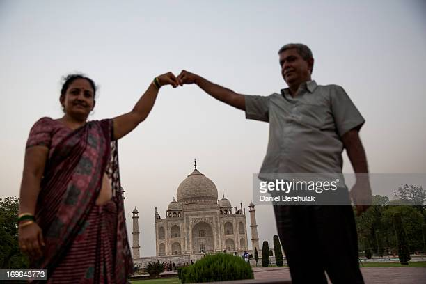 An Indian couple pose for a photograph as they visit the Taj Mahal on May 29 2013 in Agra India Completed in 1643 the mausoleum was built by the...