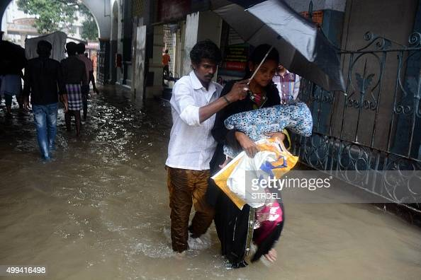 An Indian couple shelter under an umbrella as they walk with their child through floodwaters inundating Egmore Hospital in Chennai on December 1...