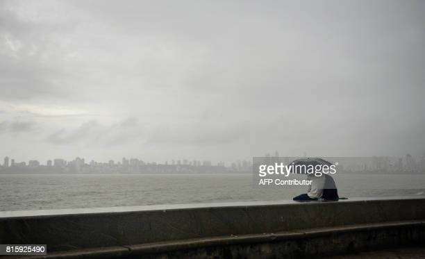 An Indian couple sits at the seafront during rain showers in Mumbai on July 17 2017 PARANJPE