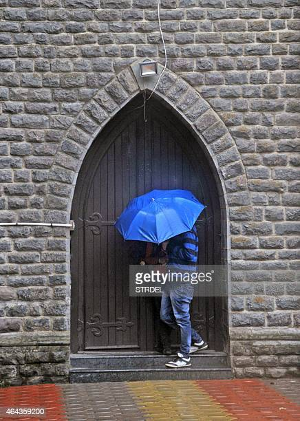 An Indian couple take shelter in a doorway of a church during heavy rainfall in Shimla on February 25 2015 AFP PHOTO/STR