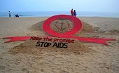 An Indian couple walks past a sand sculpture on the eve of World AIDS Day created by sand artist Sudarsan pattnaik on Golden Sea Beach in Puri some...