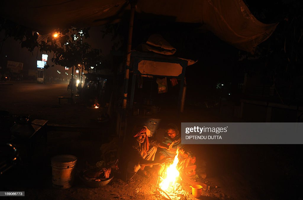 An Indian couple warm themselves at a fire next to their roadside stall in Siliguri on January 7, 2013. As thousands of homeless people sought places in temporary shelters, the unusual cold in throughout India has been attributed to dense fog which has obscured the sun and disrupted airports and trains, as well as icy winds from the snowy Himalayas to the north. AFP PHOTO/Diptendu DUTTA