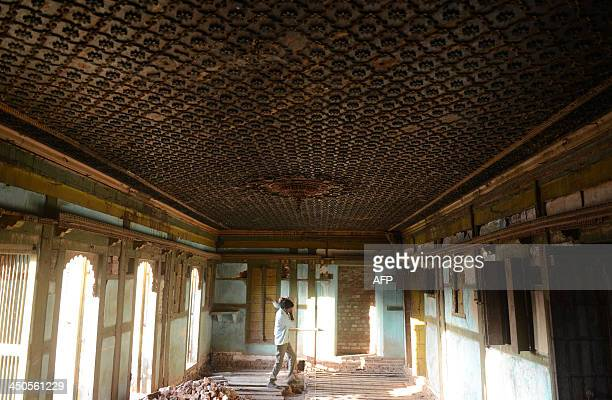 An Indian craftsman walks through the Vitthalbhai Ni Haveli in Vaso town some 60kms from Ahmedabad on November 19 on the first day of World Heritage...