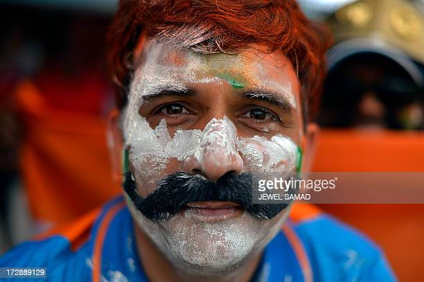 An Indian cricket fan has his face painted with national colors as he watches the fourth match of the TriNation series between India and West Indies...