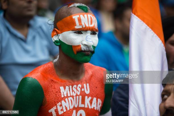 An Indian cricket fan painted with the national colours watches the action during the ICC Champions trophy match between India and Pakistan at...