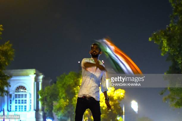 An Indian cricket supporter waves an Indian national flag as Pakistan won the ICC Champions Trophy final cricket match against India in New Delhi on...