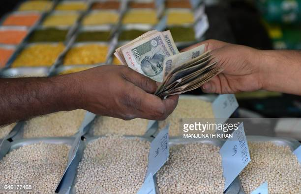 An Indian customer hands over cash to a food grain merchant at a wholesale trading shop in Bangalore on February 28 2017 India's economic growth rate...