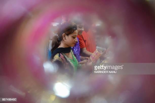 An Indian customer inspects bangles on sale in Amritsar on October 8 2017 Bangles are in heavy demand ahead of the forthcoming Karva Chauth festival...