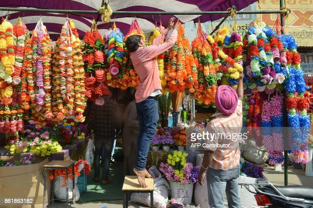 An Indian customer looks at artificial flower garlands ahead of Diwali festival at a roadside stall in Amritsar on October 16 2017 / AFP PHOTO /...