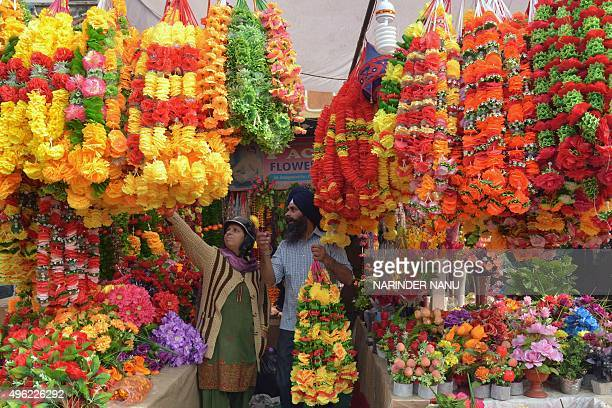An Indian customer looks at artificial flower garlands ahead of Diwali in Amritsar on November 8 2015 Flowers and decorative items are in heavy...