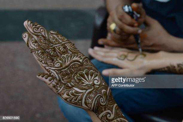 An Indian customer sits as her hand is decorated with henna on the eve of the Rakhi festival in New Delhi on August 6 20172 Young girls are having...