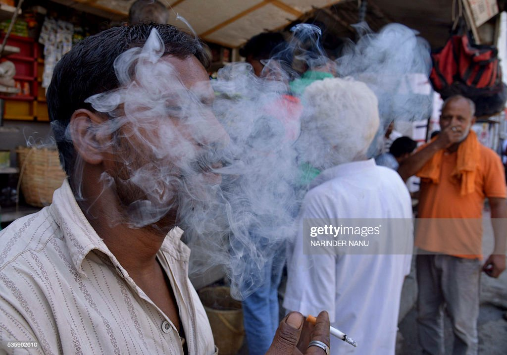 An Indian customer smokes a cigarette near a roadside stall in Amritsar on May 31, 2016, on 'World No Tobacco Day'. Many countries are considering following the example of Australia and introducing 'plain packaging' of cigarettes with graphic health warnings which are said to reduce the appeal of smoking. / AFP / NARINDER