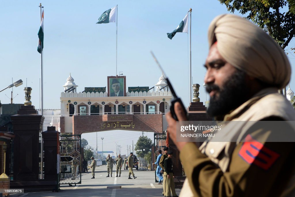 An Indian customs official (R) stands as Pakistani Rangers (C) look on at the India-Pakistan border in Wagah on January 15, 2013. Indian Prime Minister Manmohan Singh warned Tuesday that there 'cannot be business as usual' with neighbouring Pakistan after last week's deadly flare-up along the border in disputed Kashmir.