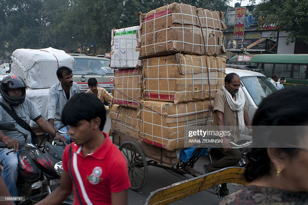 An Indian cycle rickshaw driver transports boxes of goods in the midst of heavy traffic in New Delhi on November 5, 2012. The ruling Congress party has rolled out its big guns to defend the move to let the likes of Walmart set up shop in India, but they are confronting an alliance stretching across the political spectrum. Prime Minister Manmohan Singh's left-leaning government announced in September that it was lowering the bar for foreign firms to operate in sectors ranging from retail to insurance, in a bid to revive its fortunes before elections in 2014 but elsewhere in the country, a broad array of Congress opponents are vowing to scupper the changes. AFP PHOTO/Anna ZIEMINSKI