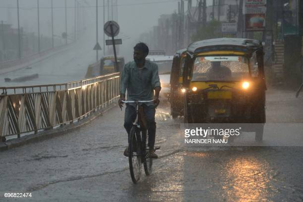 An Indian cyclist makes his way through a heavy rainstorm on a road in Amritsar on June 17 2017 Heavy rain and thunderstorms are hitting northern...