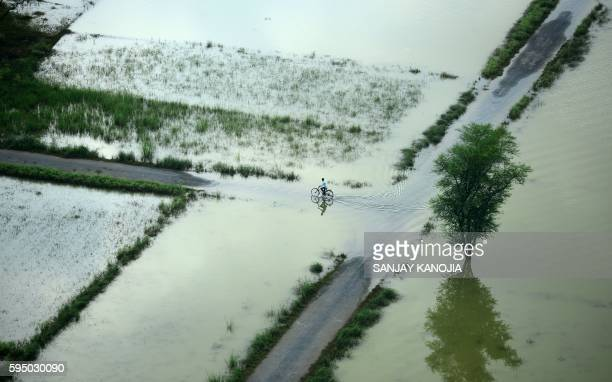 TOPSHOT An Indian cyclist rides along a flooded road on the outskirts of Allahabad on August 25 2016 At least nine people have died in Uttar Pradesh...