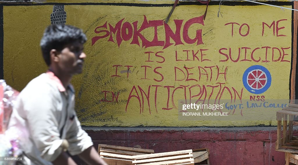 An Indian cyclist rides past anti-smoking graffiti on a wall in Mumbai on May 31, 2016, on 'World No Tobacco Day'. The World Health Organisation (WHO) is using 'Get Ready For Plain Packaging' as the slogan of this year's day. Many countries are considering following the example of Australia and introducing 'plain packaging' of cigarettes with graphic health warnings which are said to reduce the appeal of smoking. / AFP / INDRANIL