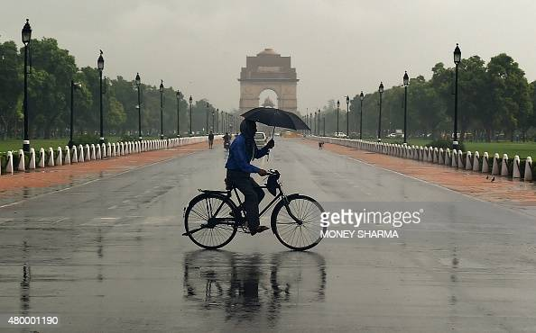 An Indian cyclist uses an umbrella as he travels across Rajpath in New Delhi on July 9 during heavy monsoon rainfall AFP PHOTO/MONEY SHARMA