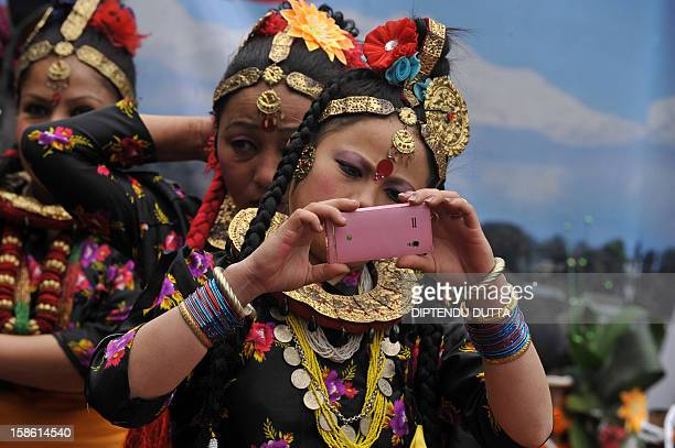 An Indian dancer uses a cellular telephone to take a photograph during a performance as a part of promotional event of The Darjeeling Tea and Tourism...
